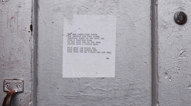 piece of white paper with typed words, a poem, pasted onto a silver coloured door