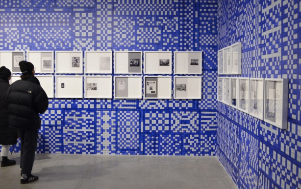 two people looking at framed pictures and pages of text on a wall that has been painted in blue and white squares