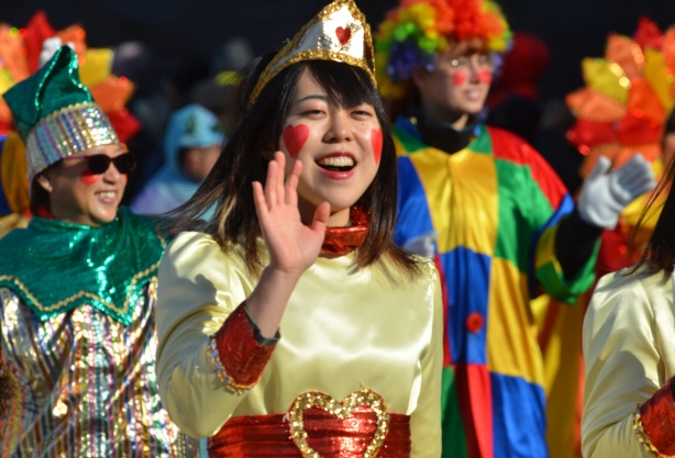 woman in gold costume as Queen of hearts in parade, heart shaped red marks on cheeks, heart on belt and on gold crown,