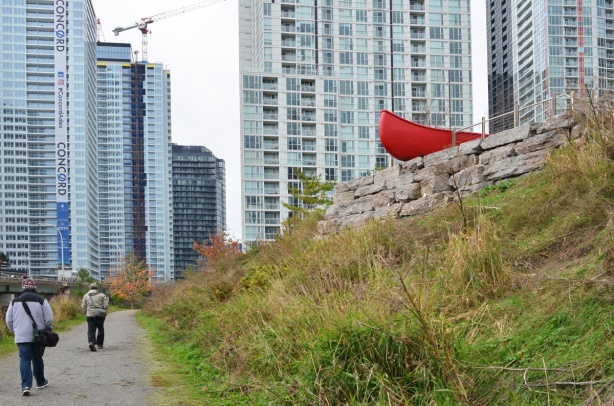 Douglas Coupland's red canoe at Canoe Landing Park sticks out of the edge of small hill, tall condo buildings in the background