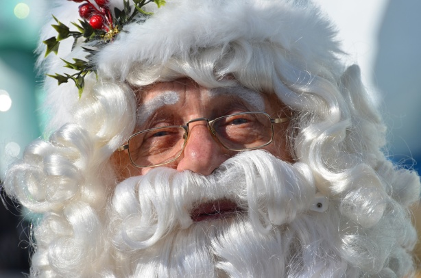 up close photo of Santa Claus's face with white beard and white mustache, some holly on his hat, glasses,
