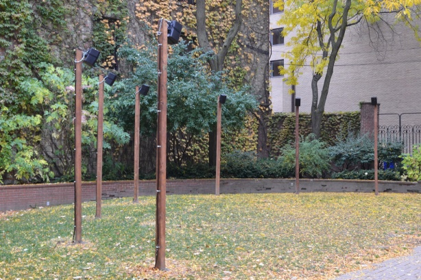 in a garden, on flat space, grass, wood poles with small speakers attached to the top of them