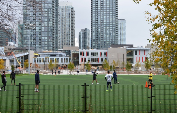men playing soccer on green fake grass playing field in front of Toronto skyline, at Canoe Landing Park