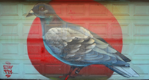 a large painting of a pigeon on a garage door in an alley