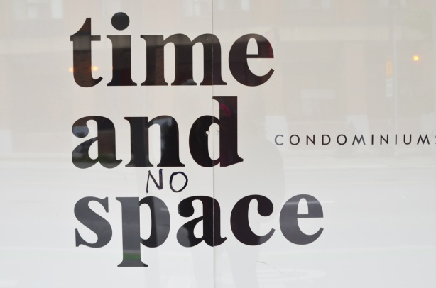 time and space condo hoardings where someone has written the word no in front of space, so you have time and no space condos