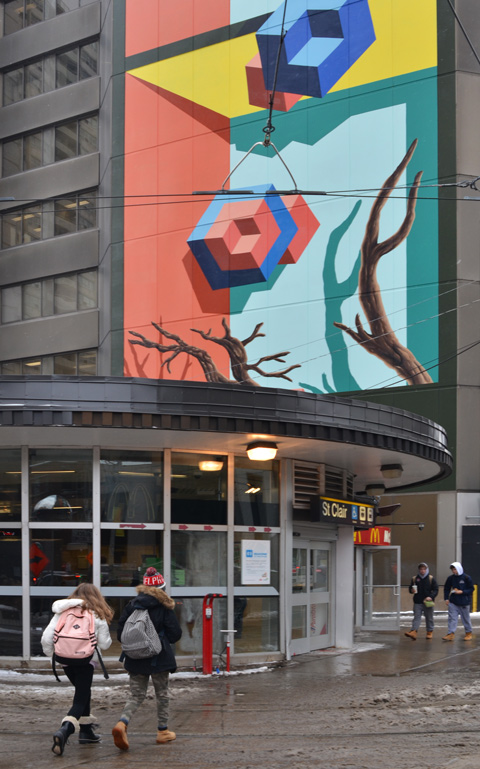 street entrance to St. Clair subway station, some people walking towards it, a large mural on the building behind it
