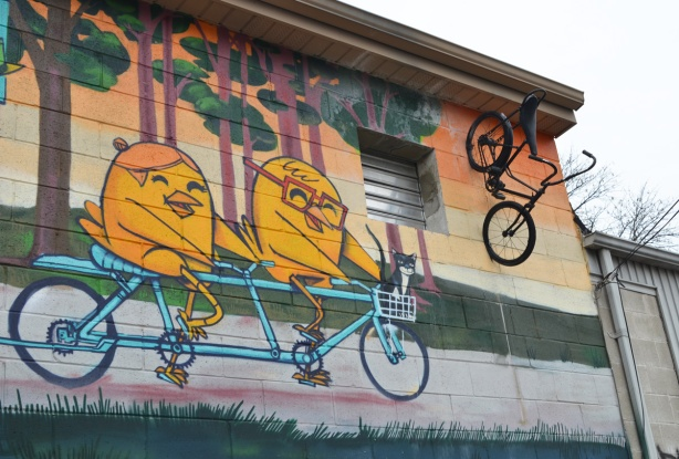 an UBer5000 mural of two yellow birdies on a tandem bike. An old bike is affixed to the wall beside the mural