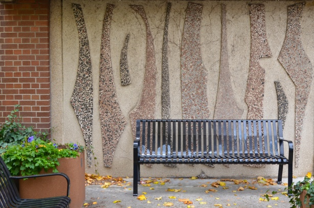 a black metal bench, outside, sits in front of a wall with an artwork on it made from different colours of concrete and pebbles