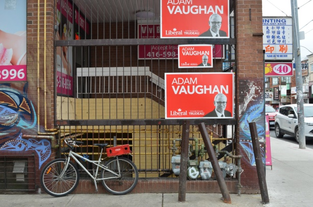 side of a building in Chinatown, stores and restaurant, bike parked there, also three large Adam Vaughan election signs.
