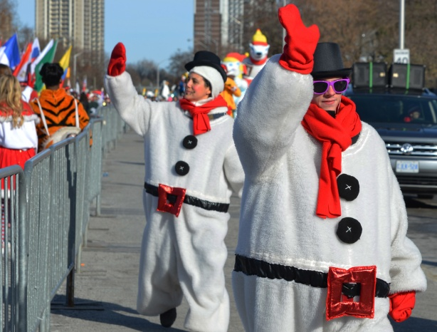 three women dressed as fat snowmen with black hats, black buttons, red scarves, and red belt buckles, waving to the crowd as they walk in the parade
