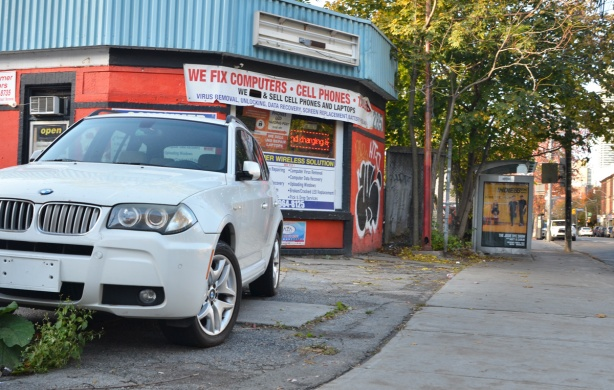 a white BMW vehicle with no front licence plate parked in front of a small old building covered with signs that say we fix computers, cell phones and wireless solutions, etc