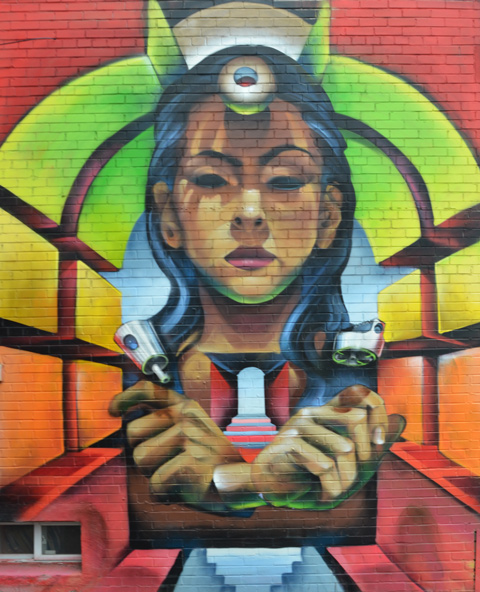mural of young woman's face, looking straight ahead, eyes partially closed, arms crossed in front of her,