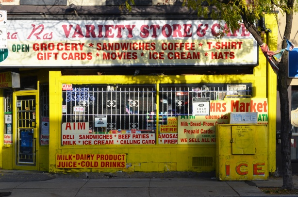 variet and convenience store painted bright yellow, white metal grill covers window, lots of signs in and around the window in red letters