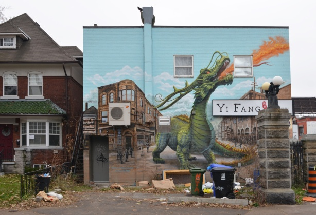 large mural on the side of abuilding, a large green dragon is breathing fire and scaring people out of their homes and stores and into the streets,