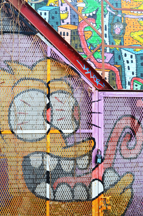 part of a mural by al runt on a wall and on a metal fence