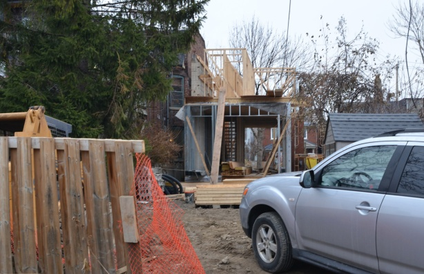 a car parked in a backyard of a house that has been gutted and is now being rebuilt