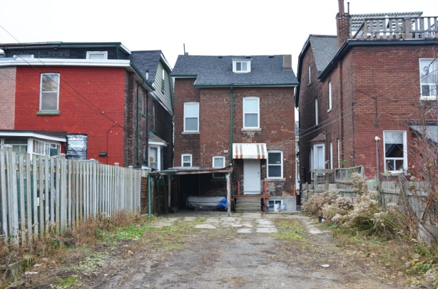 empty backyard of an older two storey building, with brick buildings on either side of it, seen from the laneway