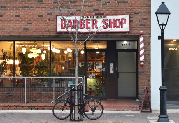 blood and bandages barber shop from the outside, lights in window, bike parked outside