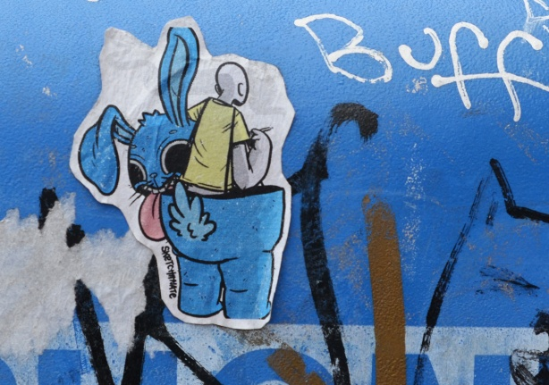 on a blue metal box, a sticker slap graffiti of a man in yellow shirt coming out of a large blue rabbit suit