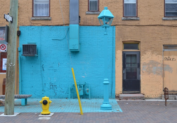part of a lower storey of a building, as well as part of the sidewalk directly in front of it, are painted bright light blue