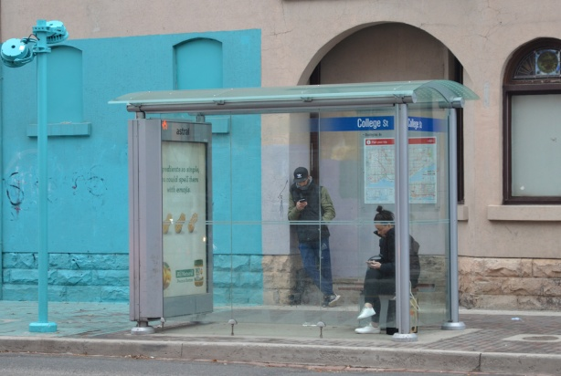 two people waiting in a TTC bus shelter, part of a lower storey of a building, as well as part of the sidewlk directly in front ot it, are painted bright light blue