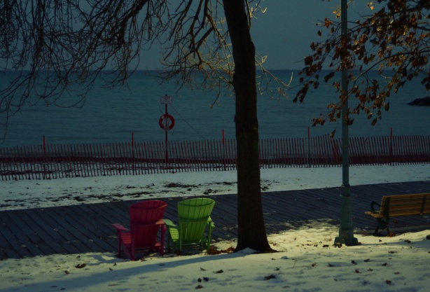 after dark, lights shining on two Muskoka chairs beside the boardwalk at Kew Beach