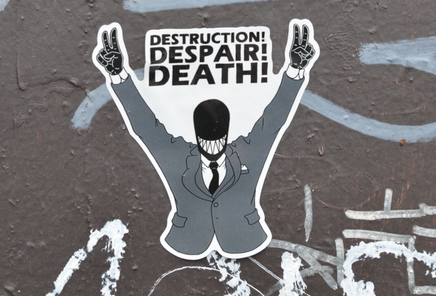 a sticker of a black faceless man in grey suit, black tie, and black gloves, with arms raised with two hands in peace symbol, words that say destruction, despair, death