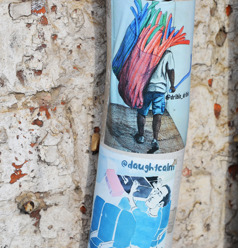 two stickers on a pole with crumbling concrete or plaster behind, top sticker is by drible_drible and the bottom is by daughtcalm
