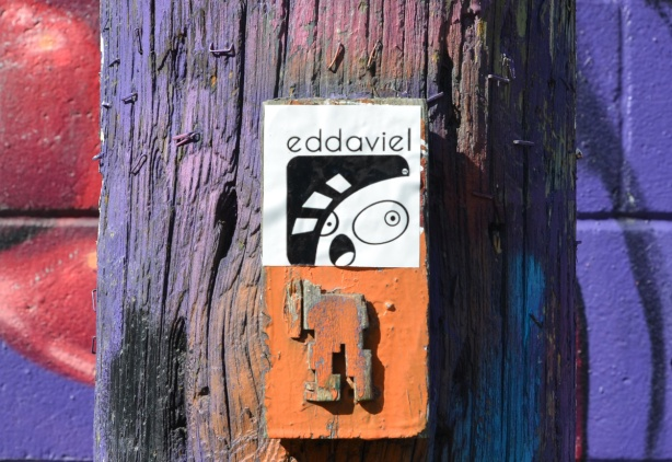 on a wood utility pole in graffiti alley, on top is a sticker with word eddoviel and on the bottom is the bottom part of an old orange stikman