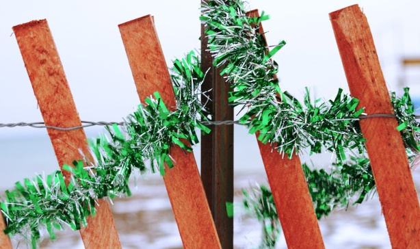 shiny green Christmas garland wrapped around part of a snow fence
