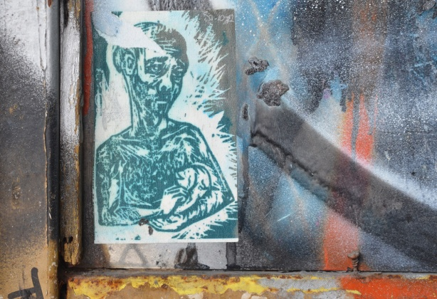 paste up in window of a man with depressed look on face, from waist up, holding a baby in his arms, in green tones