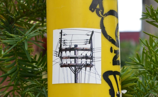 sticker of a large wood utility pole with 3 horizontal pieces, lots of wires, top part of pole only