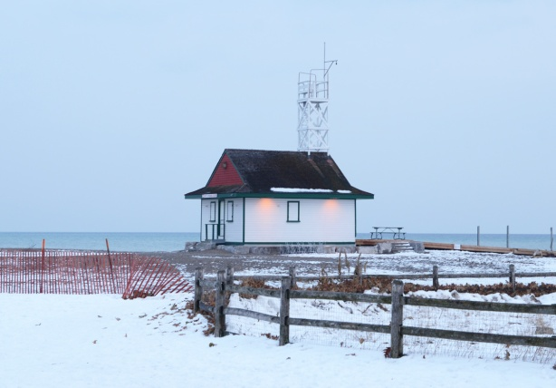 Leuty lifeguard station in late afternoon, snow fence, some snow on the ground, lights on,