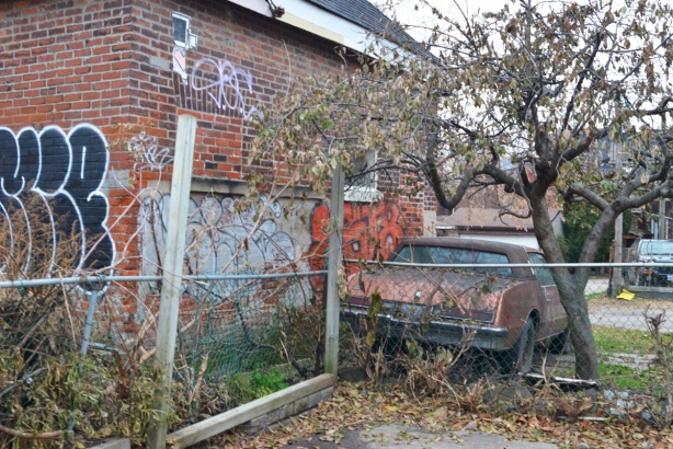 an old car is parked under a tree and beside a house with graffiti on it