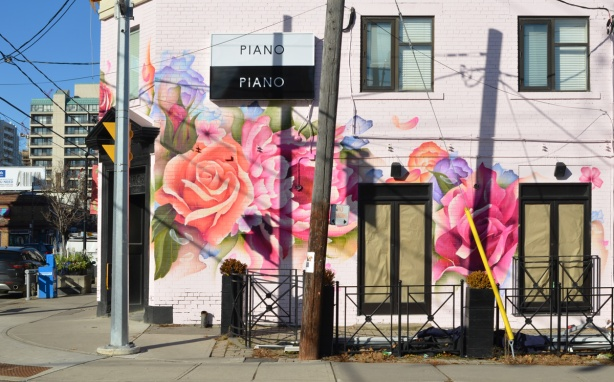 new Piano Piano restaurant on the corner of Mt. Pleasant and Manor Rd painted pink with large flowers, windows still papered over, painted by street artist bacon