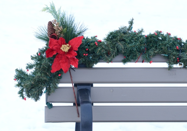 bench decorated with fake pine, pine cones and a red poinsettia flower