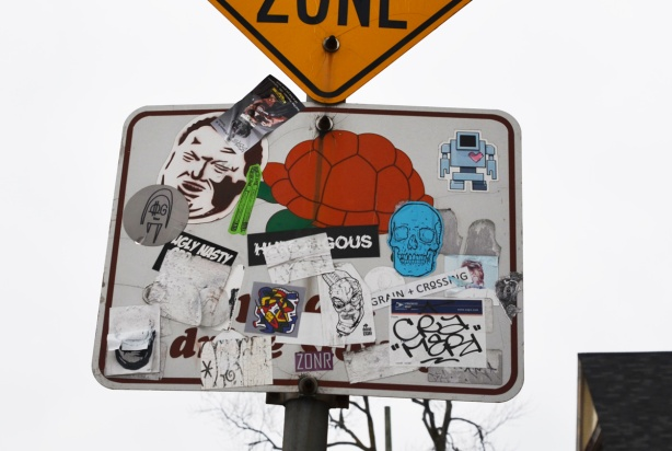 many stickers on a traffic sign, including rob ford's face and a blue skull