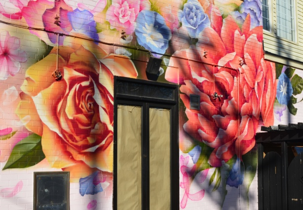 painted on exterior wall, a larege orange rose and a pink peony frame a window, other smaller flowers on top
