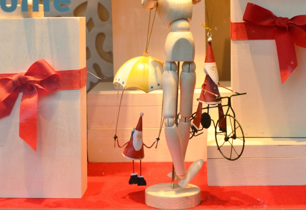 Christmas decorations in a store window, little tree ornaments of Santa, one with him holding onto a little parachute and one with him on a bike