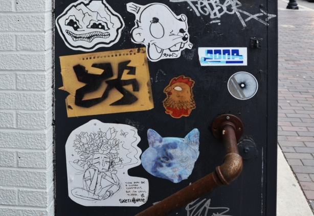 stickers and paste ups on a black box including a brown & red chicken head, a blue cat head