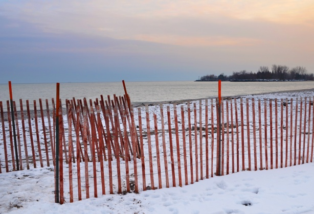 sunset behind Lake Ontario at Woodbine Beach, snow fence, some snow on the ground