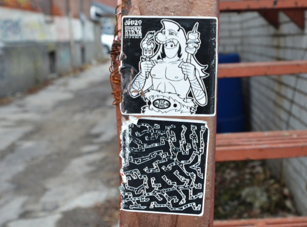 stickers and slaps on a brown railing of an exterior staircase