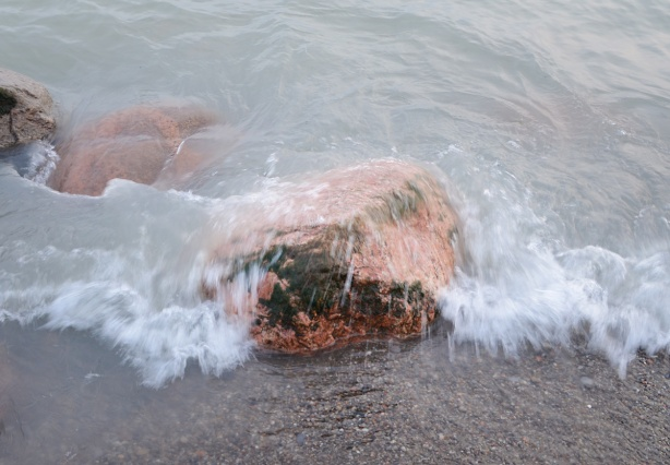 slow mo pic of waves crashing over a rock at the beach