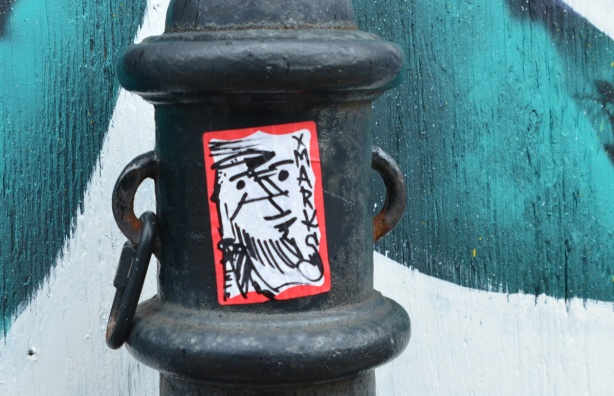 small sticker graffiti on a metal pole, street art on the wall behind. Word on sticker is xmarks