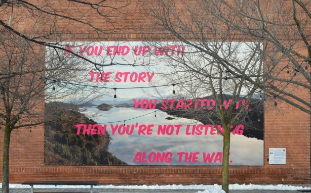 an art installation on the exterior wall of the Power Plant Contemporary Art Gallery, words in pink letters written over an river landscape scene. the words say If you end up with the story that you started with, then you're not listening along the way.
