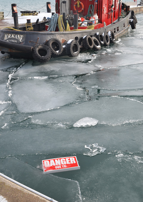 Toronto red tug boat in the water with brocken bits of ice in the water, also a red and white danger due to sign that has fallen onto the ice of Lake Ontario
