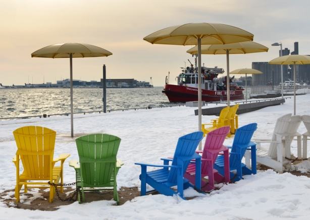 yellow umbrellas and painted muskoka chairs in the snow at H T O beach, with red fire rescus boat just offshore