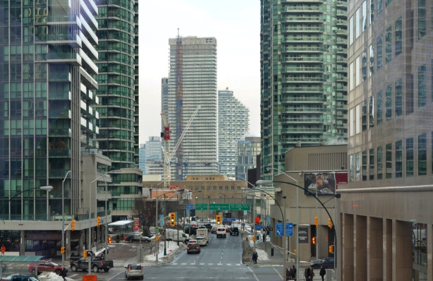 view east on Harbour Streeet from the walkway between Waterpark Place and Scotiabank Arena, construction of new high rises in the background, traffic,