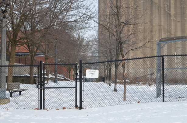 winter scene, base of Bathurst street by old Canada Malting Co silos, black gate to Ireland Park path is locked, snow, bench,