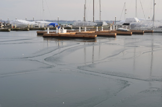 a couple of boats docked at wood docks, lakefront, waterfront, some thin ice in patches on the water between the shore and the boats. Lake Ontario